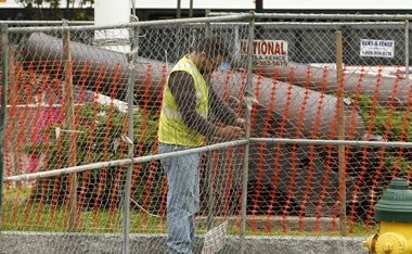 Workmen install fencing around Military Park in preparation of the start of a major reconstruction project.