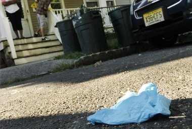An EMS worker's glove lies on the ground near where four people were shot this morning in Montclair. A woman is in serious condition.