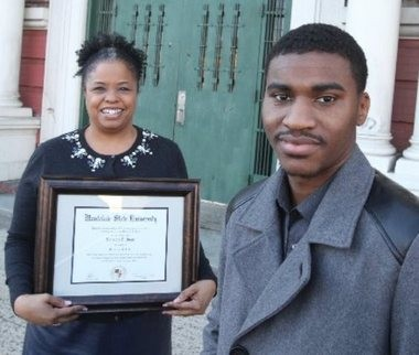 Bai-Eyse Pugh gave his eighth grade teacher Stephanie Hairston his Bachelor of Arts diploma from Montclair State University for her encouragement to continue his education. Pugh and Hairston stand in front of their old school at William H. Brown Academy in Newark on March 12, 2015.