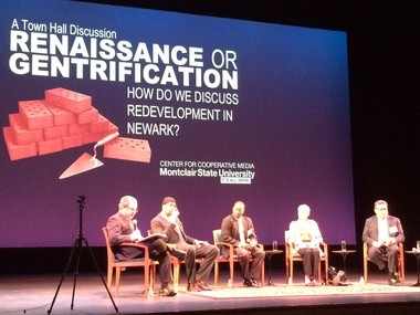 Panel members take their seats on stage at the New Jersey Performing Arts Center Monday night.