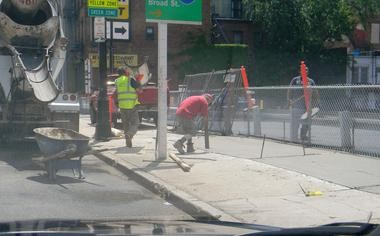 Edison Properties, a real estate company, has expanded one of 10 parking lots it owns in Newark on Central Avenue - without permission from the city's Zoning Board of Adjustment. A construction crew installs a sidewalk with city approval. The fence and guardrail haven't been approved, either.