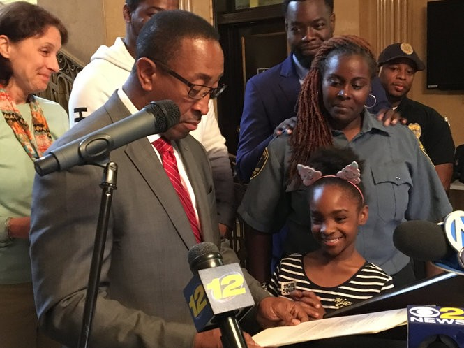 """Kori Scott, a third-grader in East Orange, was named """"Mayor for a Day"""" by Mayor Ted Green, left, after preventing a classmate from choking by performing the Heimlich maneuver. Her mother, Kiana Scott stood behind her. Her father, Roy Scott, is behind the mayor, in white."""