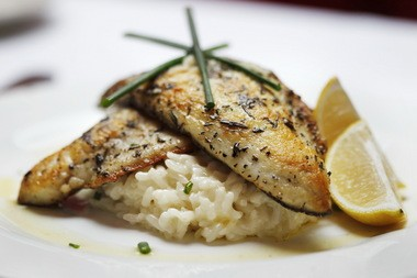 Pan- seared Mediterranean sea bass fillet with herb butter, and risotto Milanese at Fresco.
