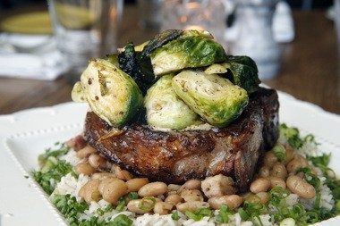 Berkshire pork porterhouse with slow cooked beans and bacon, rice and Brussels sprouts.