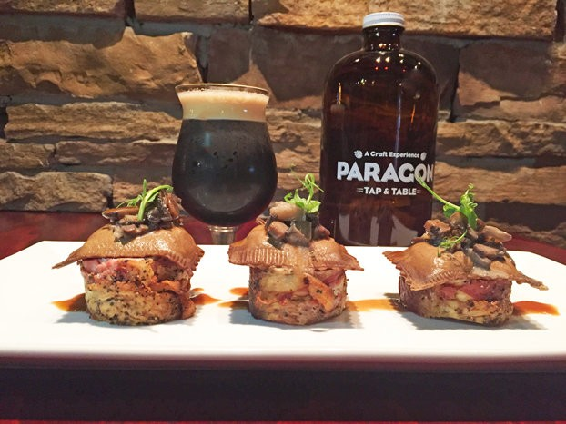 Bacon-wrapped pork lion with mushroom ravioli, mushroom ragout and mushroom chips paired with Founder's Oatmeal Stout from Paragon Table & Tap in Clark.