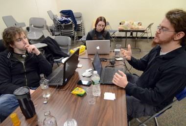 """Tim Sawicki, (left) Jennifer Rodgers, (center) and Andrew Wilson (right) discuss the final stages of development of their board game """"Subnormal"""" during the 5th annual Global Game Jam, held in part at Camden County College's Blackwood Campus, on Sunday, January 27, 2013. (Staff Photo by Joe Warner/South Jersey Times)"""