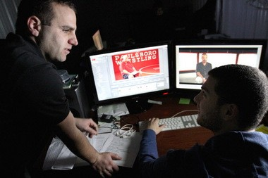 """Mike Lucas, left, and Domenick Cucinotta work on a documentary film about Paulsboro's wrestling program titles 'Home of Champions."""" They are focusing mostly on the 2011 season when the team reached its 1000th win, Thursday, Jan. 30, 2013. (Staff Photo by Tim Hawk/South Jersey Times)"""