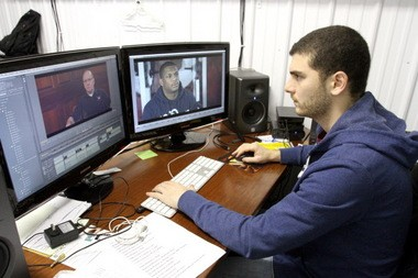 """Domenick Cucinotta edits video of former Paulsboro wrestler Isaac Redman and Olympic Gold Medalist and former University of Iowa wrestling coach Dan Gable for a documentary film about Paulsboro's wrestling program titled """"Home of Champions."""" They are focusing mostly on the 2011 season when the team reached its 1000th win, Thursday, Jan. 30, 2013. (Staff Photo by Tim Hawk/South Jersey Times)"""