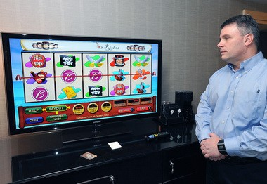 Borgata's vice-president of information technology John Forelli demonstrates in-room gaming at Borgata Hotel Casino and Spa in Atlantic City, N.J., Monday, Feb. 11, 2013. The Borgata Hotel Casino & Spa in Atlantic City said it's the first casino in the United States to let guests gamble over hotel room TV sets. Gambling from a home computer is the next step in convenience gambling, after legislation legalizing online gambling was recently signed into law. (AP Photo/The Press of Atlantic City, Michael Ein)