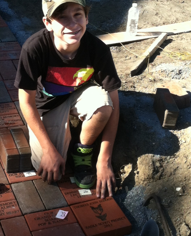 Thomas Seddon, 14, kneels over a brick dedicated to his grandfather at the new memorial garden at St. Bridget's Church in Glassboro. Thomas built the garden for his Eagle Scout project.