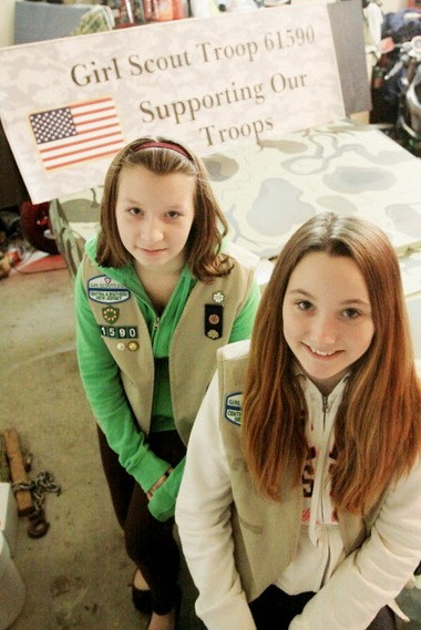 Nicole Bittman, 13, and Haley Ford, 13, of Girl Scout Troop 61590 stand in front of their float that they built for the Swedesboro Christmas Parade to collect necessary items to help soldiers when they return home, Tuesday, Nov. 26, 2013. (Staff Photo by Calista Condo/South Jersey Times)