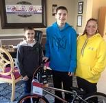 RJ Doughtry and his mother Michelle stand with his brother after Bianca's Kids donated a new BMX bike on Feb. 22, 2015. RJ had been friends with Autumn Pasqaule and enjoyed riding their bikes together. (Submitted Photo)