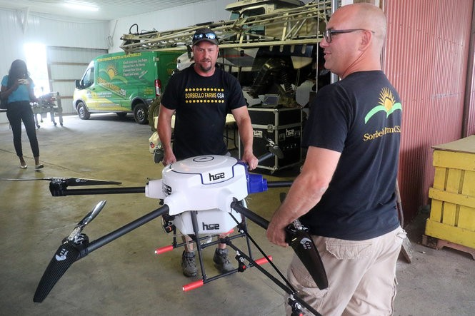 Growtopia/Sorbello Farms co-owners, Kris Wilson, right, and Steve Vazquez carry their drone outside for a demonstration flight in Woolwich Township Monday (Al Amrhein | For NJ Advance Media?
