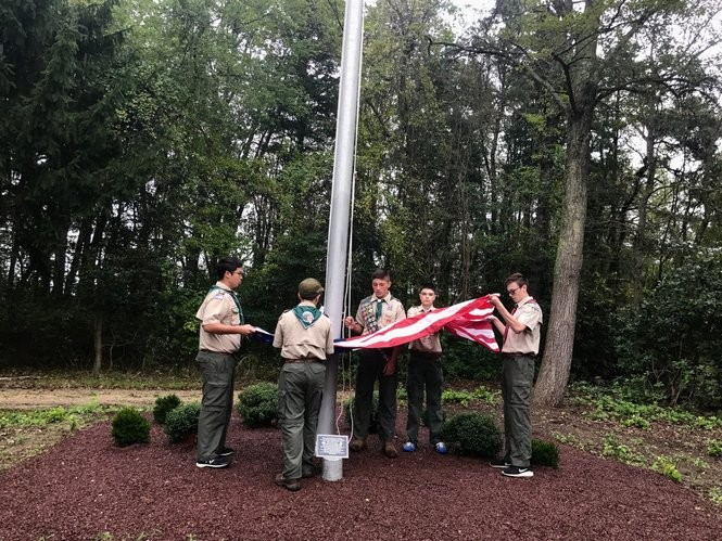 Boy Scouts Troop 60 raise a flag at the site of Operation Safe Haven.