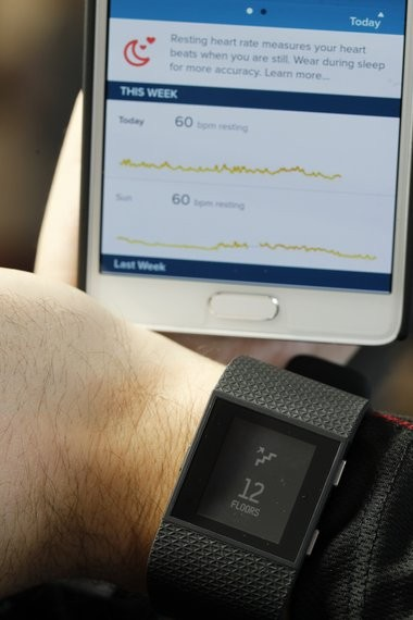 Andrew Testa with Verizon Wireless demonstrates Fitbit Surge with the Fitbit application on a smartphone.(Patti Sapone   NJ Advance Media for NJ.com)