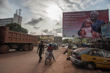"""A man walks past a poster reading """"We should not push our children away because they survived Ebola"""" on Jan. 15. Sierra Leone on Monday marked the one-year anniversary of being declared Ebola-free by the World Health Organization."""