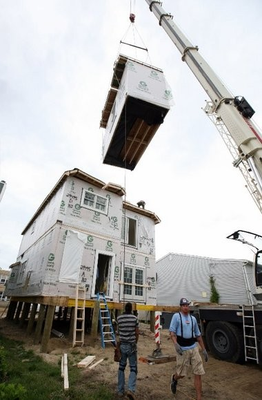 A crane places a section of a modular home being built to replace one destroyed by Hurricane Sandy in Manasquan.