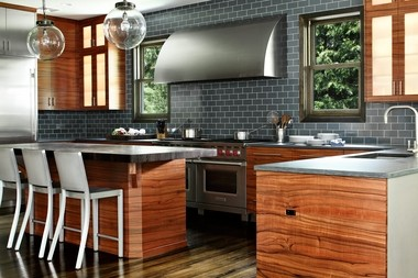 Exotic European apple wood is a warming complement for gray glass tiles and stainless steel in an award-winning Summit kitchen by designer Heidi Piron.