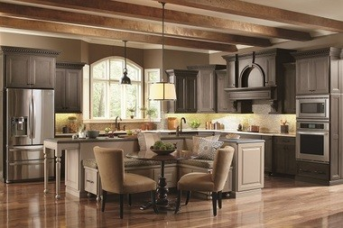 The grayish-brown Smokey Hills finish on cabinetry from Omega's Lorient collection meshes well with this kitchen's stainless steel appliances, exposed wood beams and tan accents.