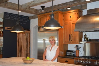 Deb Cerami of Westfield in her renovated kitchen, which has a barn-style door made of reclaimed barn wood to cover the pantry area.