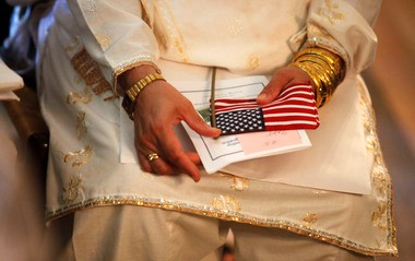 A woman holds an American flag in her lap during a recent citizenship swearing-in ceremony.