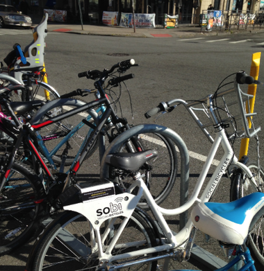 A SoBi bike is parked among other bicycles near the Hoboken Terminal.