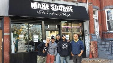 The staff of Mane Source Barbershop gather outside the store at 115 Palisade Avenue, Jersey City, NJ.