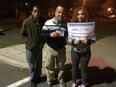 Reginald Rivera, 40, Billy O'Neill, 50, and Diany Rodriguez, 17, stand on a street corner near a polling location yesterday campaigning for repealing the city's vacancy decontrol law(Jonathan Lin | The Jersey Journal)
