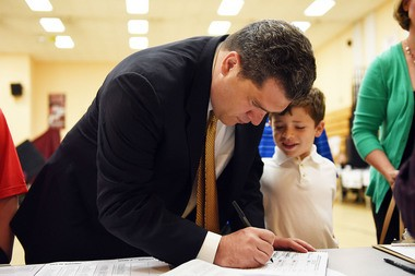 Democratic Assembly candidate for the 31st District, Nicholas Chiaravalotti, signs in to cast his vote at the Henry E. Harris Elementary School in Bayonne in the primary election on Tuesday, June 2, 2015, as his son, Joshua, 5, looks on. Reena Rose Sibayan | The Jersey Journal