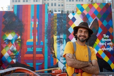 International mural artist, Eduardo Kobra, stands in front of his mural of Bob Dylan in downtown Minneapolis.