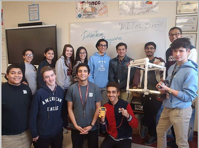 """The future Bayonne InvenTeam poses with their concept model - """"MIT or Bust!"""" All students are in 9-11th grade this year. From the left in back: chemist Marina, artist Samantha, math/statistician Danielle, documentation Melissa, coder/modeler Michael, biologist Cisco, lead engineer and co-captain Arhum (holding the concept model), and prototype/hack team Chris. From the left in front: intellectual property researcher Cyril, prototype/hack team Alex, chemist/physicist Abanoub, business manager and co-captain Mark (with meter) and prototype/hack team Frankie, (with the drill), and coder Joey not pictured."""