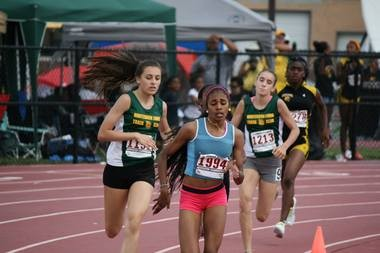 Anna DiMarcello, left, of the Hunterdon Lions Track Club is about to make a closing run in the 800-meter race to win the age 13-14 Junior Olympics state championship in Palisades Park. Teammate Carmen King (No. 1213) finished fifth. (Photo by Jim Crossin)