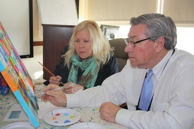 Eileen Rafferty, owner of The Paint Party Studio in Flemington, looks on as Robert P. Wise, President and CEO of Hunterdon Healthcare, paints his interpretation of a heart on the âWe Love Hunterdonâ canvas.