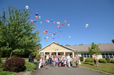 Pictured are community members releasing environmentally-friendly balloons with special notes inside.