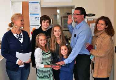 Township Clerk Michele Bobrowski administers the oath of office to Christian Pfefferle with the aid of Pfefferle's children Gabriella , Jon Ryan, Jillian and Lila and his wife Teresa.