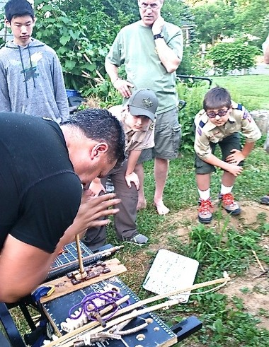 Scouts from Boy Scout Troop 108 get a lesson from 'Sensei' Joe Lau on fire making techniques. Pictured, Joe is demonstrating the fire making practice called a hand drill. After about a moment's effort, the friction created a small spark which ignited saw dust into a small flame. (courtesy photo)