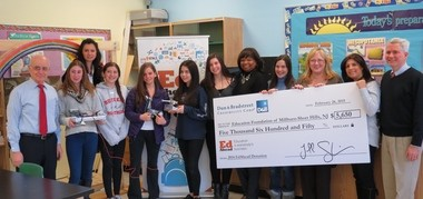 On Feb. 27, representatives from Dun & Bradstreet Credibility Corp.'s New York office present a check representing the grant of $5,650 received by the Education Foundation of Millburn-Short Hills to fund Millburn Middle School's science, technology, engineering, and math (STEM) programs. Pictured (front row, from left) is robotics teacher Lester Greenberg, Lilly Rothberg, Dr. Christine Burton, Emily Echavarria, Brigitte Muller, Rachel Williams, Katie Darvin, Brenda Gary, D&B VP Marketing Operations, Randi Little, Sheila Bouri and Amy Talbert, co-presidents, Education Foundation of Millburn-Short Hills, and Principal Michael Cahill. (courtesy photo)