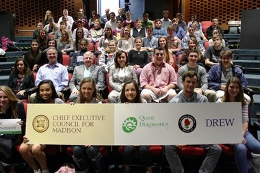 Executives Dennis Bone and Noreen Beaman sit alongside Mayor Robert H. Conley as well as Madison High School and Drew University students for a group photo after closing remarks from executive panelists at a presentation focused on leadership. (courtesy photo)
