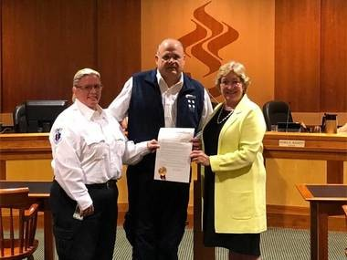 Summit Volunteer Rescue Squad president John Buscaino (center) and chief Kari Phair accept proclamation from Mayor Nora Radest.