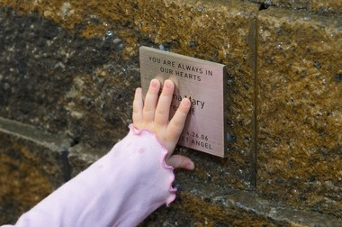 Grace Festoff touches her little sisters memorial plaque in The Angel Garden at Virtua Voorhees hospital.