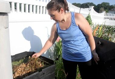 Barbara Grant, of Mantua, shows her composting bin in her backyard.