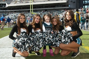 Malia Makaila (left) Deonna Baquero (second from left) and other cheerleaders pose with a little fan at an Eagles game.