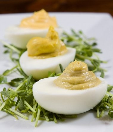 Deviled eggs in three flavors (Caesar, truffle oil and curry) on pea shoots.