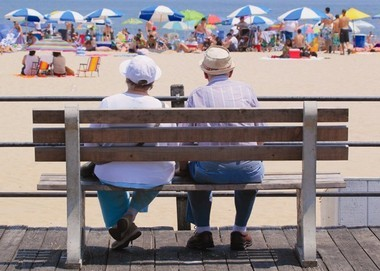 A couple shares a quiet moment on a Point Pleasant Beach boardwalk bench, while sunworshippers enjoy a warm day on the sand.