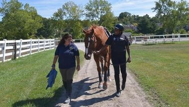 Trainer Carly Eastern, left, walks with Pat Battle and Copenhagen as they head back to the barn after a riding session.