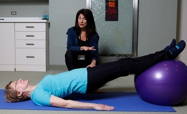 Carol Michaels, the exercise specialist, explains to patient Colleen Russo how an exercise ball can help her gain strength and stamina.