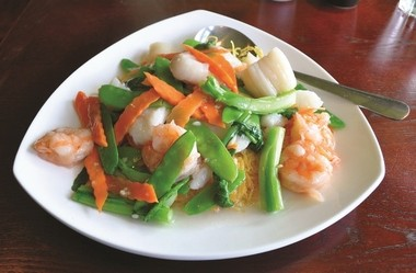 Seafood pan-fried noodles is a Cantonese dish of thin egg noodles, with flounder, scallops and shrimp, at Fusion Bay.