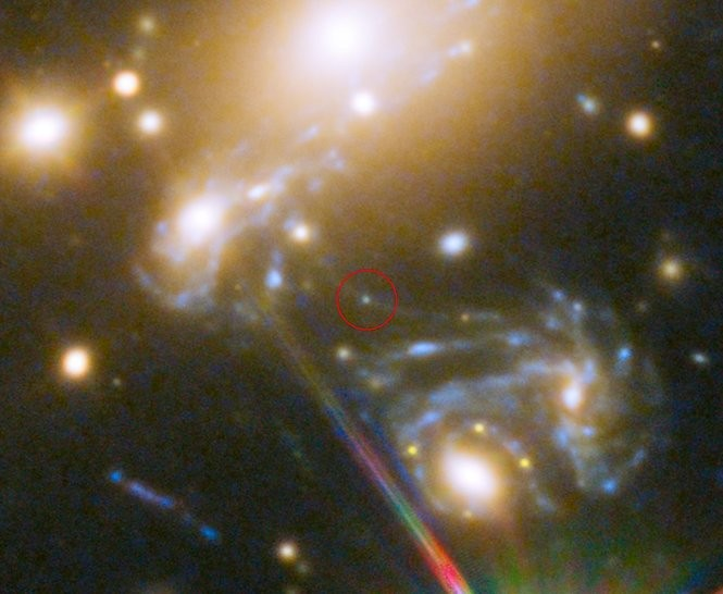 This close-up of the galaxy cluster shows the position of the star Icarus. A foreground star acted as a natural magnifying glass, allowing astronomers using the Hubble Space Telescope to discover Icarus, which is located 9 billion light years away.