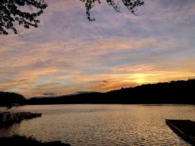 Sunset over White Meadow Lake in Rockaway, NJ. Shorter days and earlier sunsets are caused by the seasons, not Daylight Saving Time.