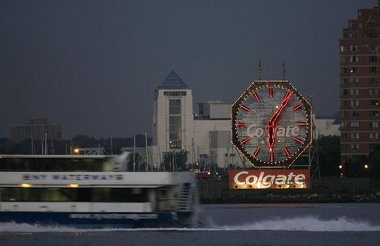 A NY Waterway ferry streaks past the Colgate Clock as seen from Lower Manhattan, August 2007.